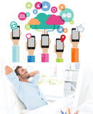 Composite image of casual man resting with hands behind head in office Stock Images
