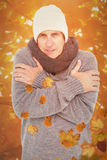 Composite image of casual man shivering in warm clothing Royalty Free Stock Images