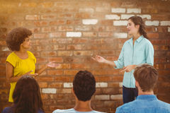 Composite image of casual young businesswoman giving presentation to colleagues Royalty Free Stock Images