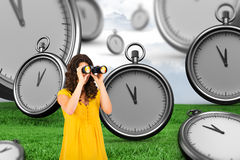 Composite image of casual young woman using binoculars. Casual young woman using binoculars against grey sky over field Stock Photos