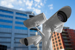 Composite image of cctv camera. CCTV camera against modern buildings against sky Stock Images