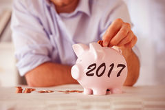 Composite image of change being put into piggy bank. Change being put into piggy bank against digital image of new year 2017 Royalty Free Stock Photo
