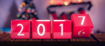 Composite image of changing cube with number. Changing cube with number against defocused of christmas tree lights and fireplace Stock Photo