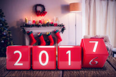 Composite image of changing cube with number. Changing cube with number against fireplace decorate with christmas decor and ornaments Stock Photo