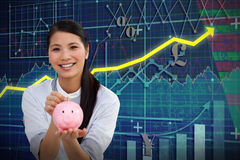 Composite image of charming businesswoman saving money in a piggybank. Charming businesswoman saving money in a piggybank against red arrow Stock Photos