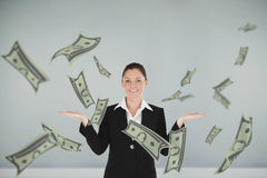 Composite image of charming woman in suit showing dollars Stock Image