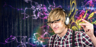 Composite image of cheerful blond hipster listening to music Royalty Free Stock Photo