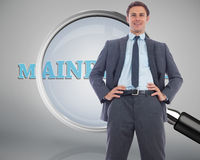 Composite image of cheerful businessman with hands on hips. Cheerful businessman with hands on hips against magnifying glass showing mainframe word Stock Photography