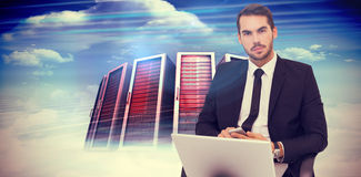 Composite image of cheerful businessman with laptop using smartphone Royalty Free Stock Photos