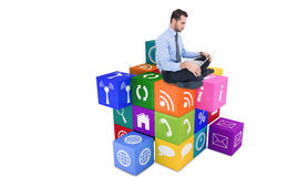 Composite image of cheerful businessman sitting on the floor using laptop Stock Images