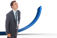Composite image of cheerful businessman standing with hand on hip Stock Images