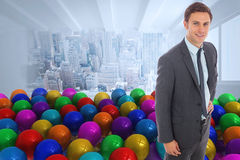 Composite image of cheerful businessman standing with hand on hip Royalty Free Stock Photography