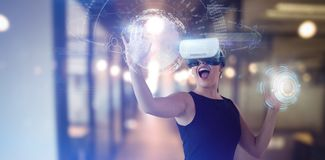 Composite image of cheerful businesswoman gesturing while looking through virtual reality simulator Stock Photos