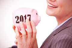 Composite image of cheerful businesswoman holding a piggybank stock photo