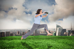 Composite image of cheerful classy businesswoman jumping while holding binoculars Royalty Free Stock Image