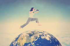 Composite image of cheerful classy businesswoman jumping while holding binoculars Royalty Free Stock Images