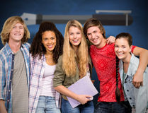 Composite image of cheerful college students in library. Cheerful college students in library against blue chalkboard Royalty Free Stock Photo