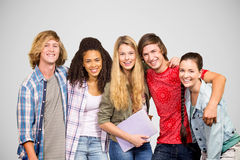 Composite image of cheerful college students in library. Cheerful college students in library against grey vignette Stock Image