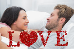 Composite image of cheerful couple awaking and looking at each other Stock Photo