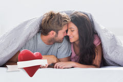 Composite image of cheerful couple head against head under the duvet Royalty Free Stock Image