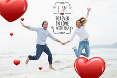 Composite image of cheerful couple holding hands and jumping at beach. Cheerful couple holding hands and jumping at beach against valentines message stock image