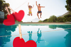 Composite image of cheerful couple jumping into swimming pool. Cheerful couple jumping into swimming pool against hearts hanging on a line Royalty Free Stock Images
