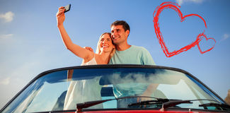 Composite image of cheerful couple standing in red cabriolet taking picture Stock Image