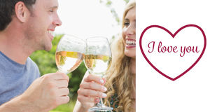 Composite image of cheerful couple toasting with white wine Royalty Free Stock Images