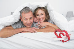 Composite image of cheerful couple under the duvet Stock Image