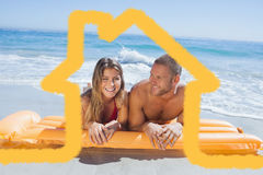 Composite image of cheerful cute couple in swimsuit lying on the beach Stock Photography