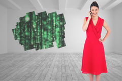 Composite image of cheerful elegant brunette in red dress on the phone posing Stock Photo