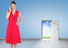 Composite image of cheerful elegant brunette in red dress on the phone posing Royalty Free Stock Photography