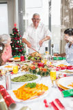 Composite image of cheerful family at dining table for christmas dinner stock images