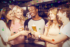 Composite image of cheerful friends toasting with beer and wine. Cheerful friends toasting with beer and wine against flying colours Royalty Free Stock Photos
