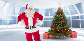 Composite image of cheerful santa claus with his hands on hips Stock Photo