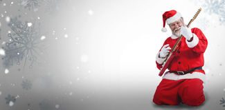 Composite image of cheerful santa claus kneeling and playing guitar Stock Photo