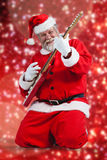 Composite image of cheerful santa claus kneeling and playing guitar Stock Image