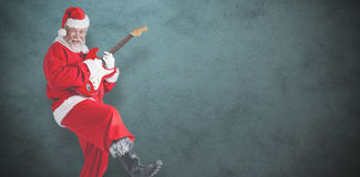 Composite image of cheerful santa claus playing guitar Stock Photos