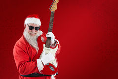 Composite image of cheerful santa claus playing guitar Stock Photo