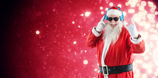 Composite image of cheerful santa claus showing hand sign while listening to music on headphones Royalty Free Stock Photography