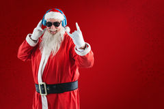 Composite image of cheerful santa claus showing hand sign while listening to music on headphones Royalty Free Stock Image