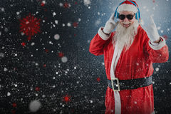 Composite image of cheerful santa claus showing hand sign while listening to music on headphones Royalty Free Stock Images