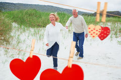 Composite image of cheerful senior couple running at beach Royalty Free Stock Image