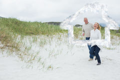 Composite image of cheerful senior couple walking at beach. Cheerful senior couple walking at beach against house outline in clouds Royalty Free Stock Photography