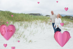 Composite image of cheerful senior couple walking at beach. Cheerful senior couple walking at beach against valentines love hearts royalty free stock images