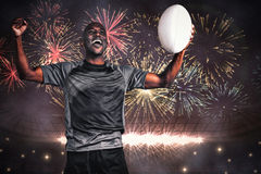 Composite image of cheerful sportsman with clenched fist holding rugby ball Stock Images