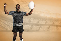 Composite image of cheerful sportsman with clenched fist holding rugby ball Royalty Free Stock Photo