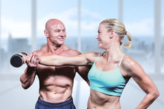 Composite image of cheerful trainer helping woman for lifting dumbbell. Cheerful trainer helping women for lifting dumbbell against bright white room with Stock Images