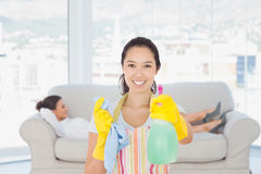 Composite image of cheerful woman holding up spray bottle. Cheerful women holding up spray bottle against smiling business women lying down on the couch Royalty Free Stock Photos