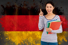 Composite image of cheerful woman pointing up while holding files Royalty Free Stock Photos